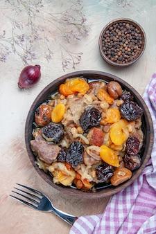 Vue de dessus pilaf un appétissant fourchette pilaf oignon poivre noir la nappe