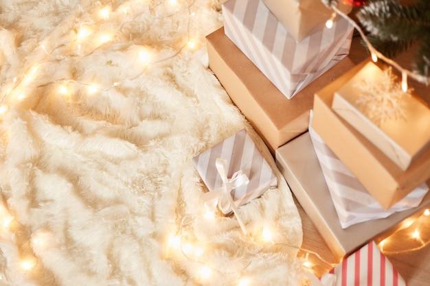 Vue de dessus de la pile de cadeaux avec des guirlandes lumineuses allongées sur un tapis blanc doux, célébration de noël, espace de copie pour la publicité.