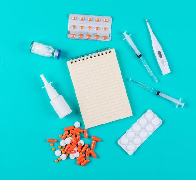 Vue de dessus des pilules avec bloc-notes, aiguilles, thermomètre et vaporisateur nasal