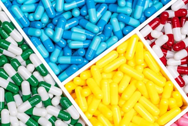 Vue de dessus des pilules de capsules antibiotiques colorées dans une boîte en plastique