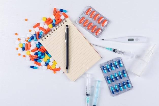 Vue de dessus des pilules colorées avec bloc-notes, stylo, thermomètre, vaporisateur nasal et aiguille