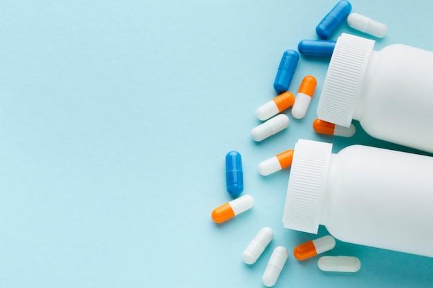 Vue de dessus des pilules colorées et des bouteilles en plastique