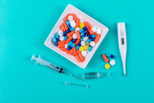 Vue de dessus des pilules dans un bol avec thermomètre et seringue