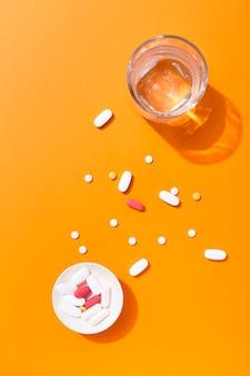 Vue de dessus des pilules dans un bol avec un verre d'eau