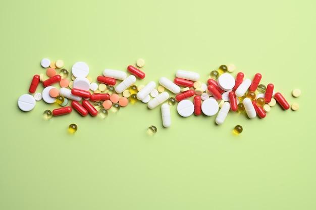 Vue de dessus des pilules lumineuses colorées sur une surface vert pastel