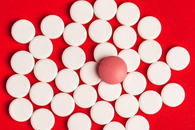 Vue de dessus des pilules de médecine pharmaceutique sur rouge