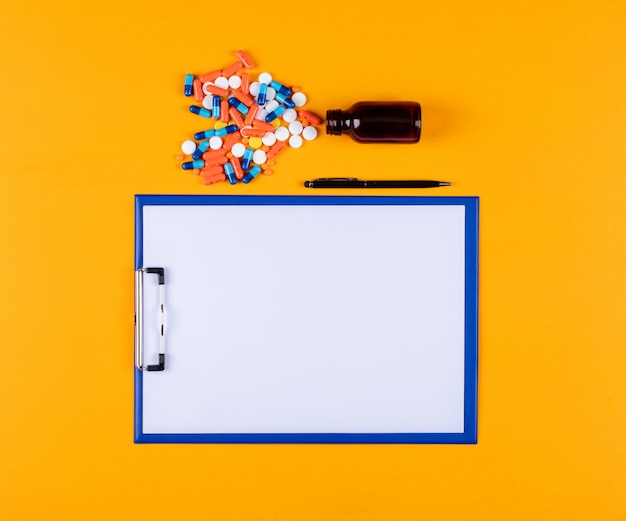 Vue de dessus des pilules avec porte-papier et stylo