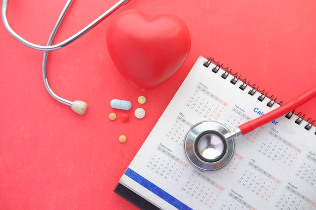 Vue de dessus des pilules et stéthoscope sur calendrier