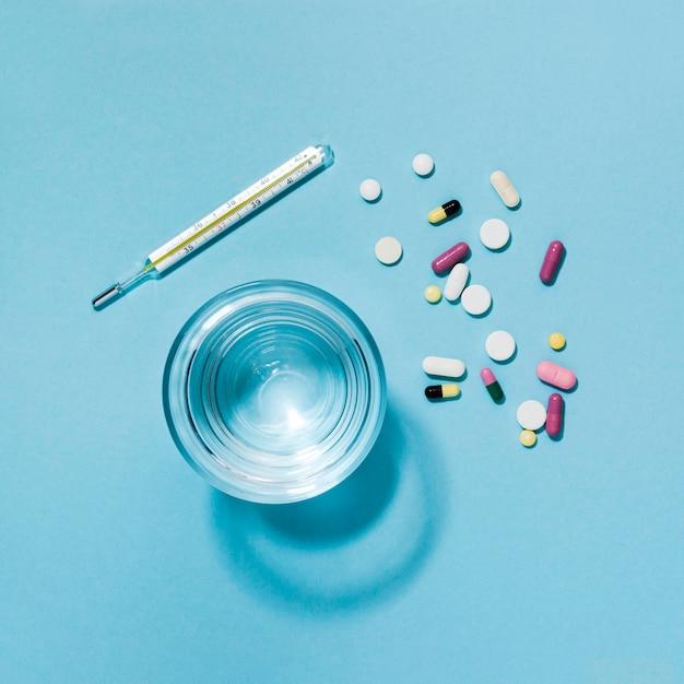 Vue de dessus des pilules avec thermomètre et verre d'eau
