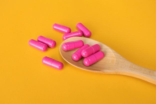 Vue de dessus des pilules de vitamines et de minéraux sur une cuillère en bois sur un espace jaune, produit de soins de santé