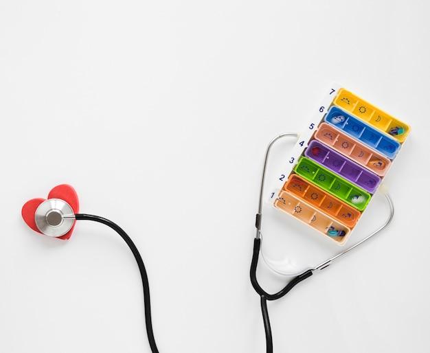 Vue de dessus pilulier coloré avec stéthoscope