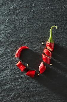 Vue de dessus, piment rouge haché sur une surface de béton noir