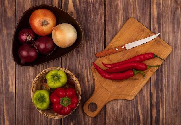 Vue de dessus des piments frais sur une planche de cuisine en bois avec un couteau avec des oignons sur un bol avec des poivrons sur un seau sur un mur en bois