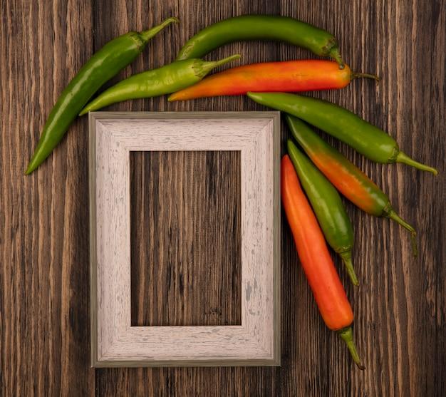 Vue de dessus des piments orange et verts isolés sur un mur en bois avec espace copie