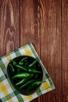 Vue de dessus de piments verts frais dans un bol sur une serviette à carreaux sur fond rustique en bois avec copie espace