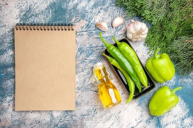 Vue de dessus piments verts sur plaque noire piments à l'ail bouteille d'huile un cahier sur fond bleu-blanc