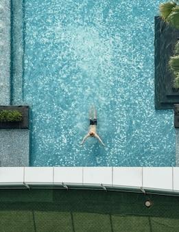 Vue de dessus de la piscine avec bar flottant et un homme nageant en été.
