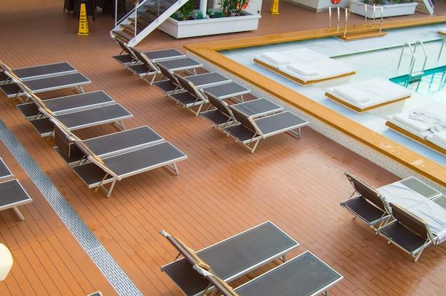 Vue de dessus de la piscine de luxe avec chaises longues vides sur le pont ouvert d'un paquebot de croisière moderne