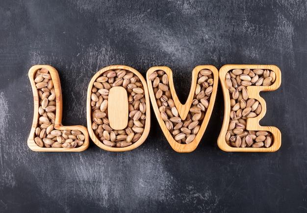 Vue de dessus des pistaches en plaques en bois en forme d'amour sur la texture grise horizontale