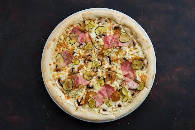 Vue de dessus de la pizza au bacon, aux champignons, au concombre mariné et à l'oignon caramélisé