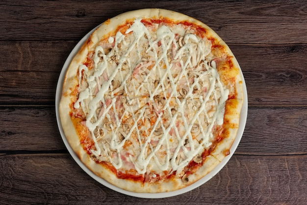 Vue de dessus de la pizza au filet de poulet, champignon, bacon et fromage