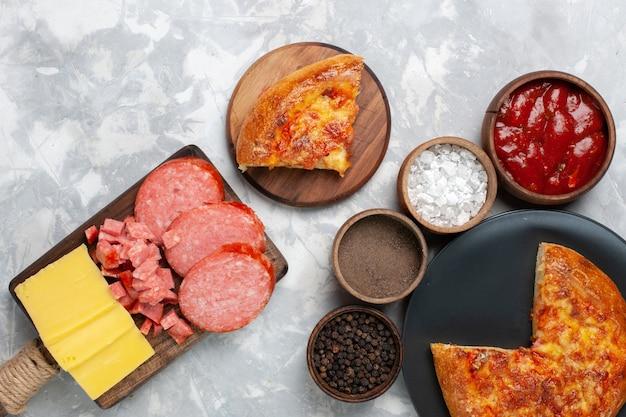 Vue de dessus pizza au fromage cuit au four avec assaisonnements sur blanc