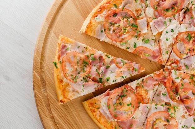 Vue de dessus de la pizza coupée sur 8 morceaux et un poussé vers l'avant