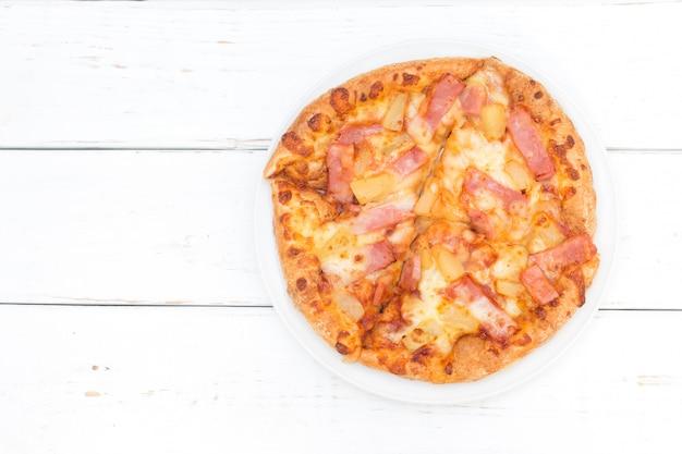 Vue de dessus de la pizza hawaïenne sur fond de table en bois blanc.