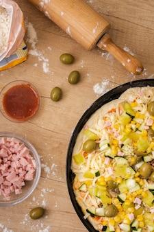 Vue de dessus pizza non cuite dans une casserole avec ingrédients et rouleau à pâtisserie