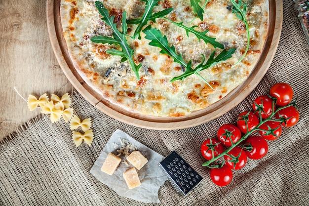 Vue de dessus pizza quatre fromages à la roquette sur fond en bois. cuisine italienne. snack et restauration rapide. photo de nourriture horizontale. pizza aux ingrédients sur la table. délicieuse pizza avec espace copie