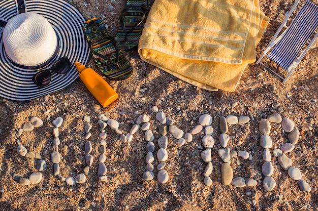 Vue de dessus de la plage de sable en bord de mer, les articles de plage sont disposés sur le sable. le mot été est en pierre