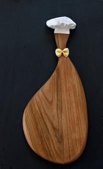 Vue de dessus d'une planche à découper en bois et une hotte, la forme du chef.