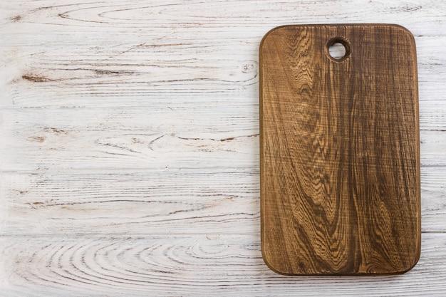 Vue de dessus d'une planche à découper en bois sur une vieille table en bois
