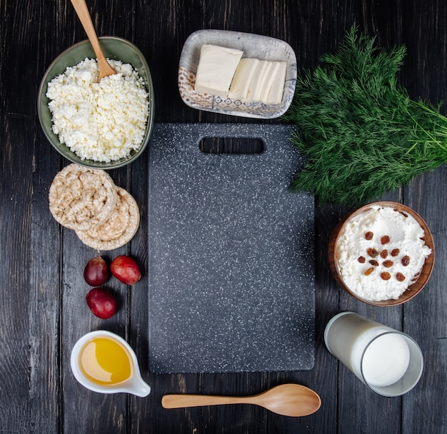 Vue de dessus de la planche à découper de cuisine et du fromage cottage dans des bols, des gâteaux de riz un verre de lait et de miel dans une soucoupe au fenouil sur tableau noir