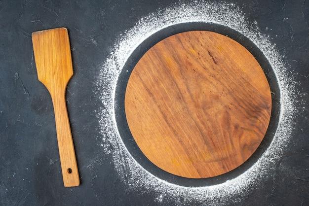 Vue de dessus d'une planche à découper ronde avec de la farine autour d'une cuillère en bois sur fond de couleur sombre avec espace libre