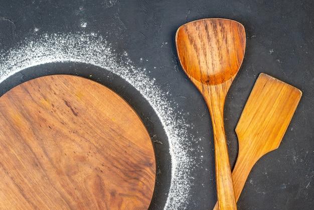 Vue de dessus d'une planche à découper ronde avec de la farine autour d'une cuillère en bois sur fond de couleur sombre