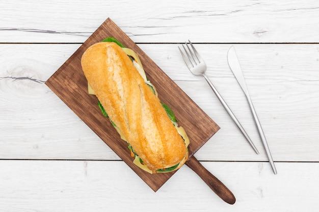Vue de dessus de la planche à découper avec sandwich sur le dessus