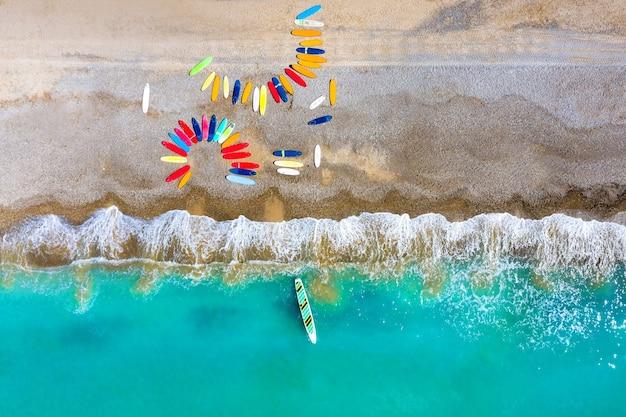 Vue de dessus des planches de surf colorées gisant de façon chaotique sur une plage de galets en france.
