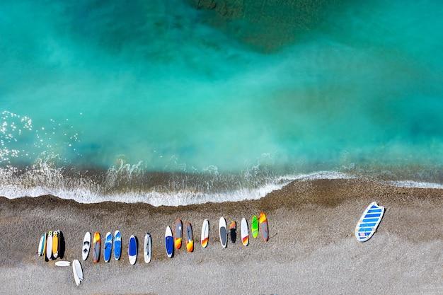 Vue De Dessus Des Planches De Surf Colorées Gisant De Manière Chaotique Sur Une Plage De Galets. Photo Premium