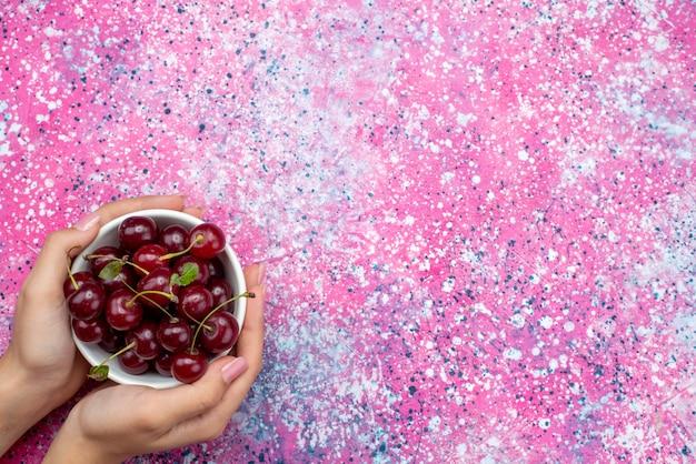 Vue de dessus plaque blanche avec des cerises fraîches rouges aigres tenant par femme sur le fond de couleur vive fruit couleur aigre