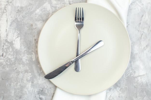 Vue de dessus plaque blanche avec fourchette et couteau sur fond clair cuisine nourriture féminité couleur repas dames horizontales verre photo