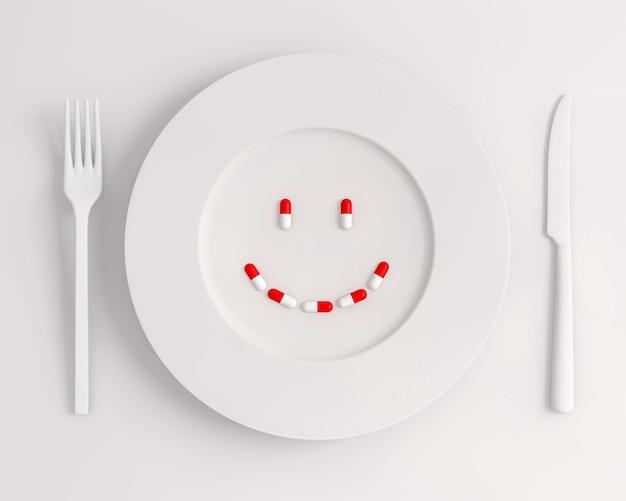 Vue de dessus plaque blanche avec des pilules formant un sourire fourchette et couteau