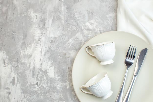 Vue de dessus plaque blanche avec des tasses fourchette et couteau sur fond clair cuisine verre alimentaire dames féminité couleurs repas horizontal