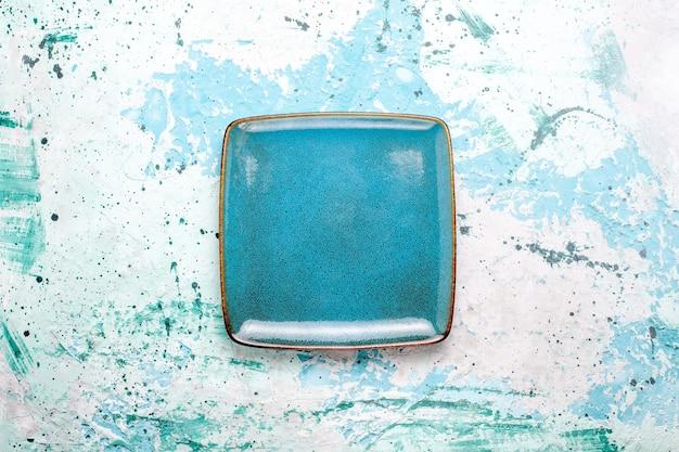 Vue de dessus plaque carrée de couleur bleue vide sur plaque de surface bleu clair couleur verre alimentaire