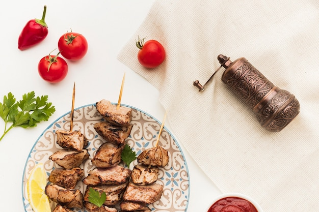Vue de dessus de la plaque avec un délicieux kebab et un moulin à condiments