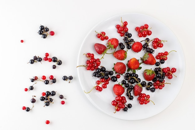 Vue de dessus de la plaque avec des fraises fraîches et moelleuses avec des myrtilles et des canneberges sur le fond blanc couleur fruits frais moelleux berry