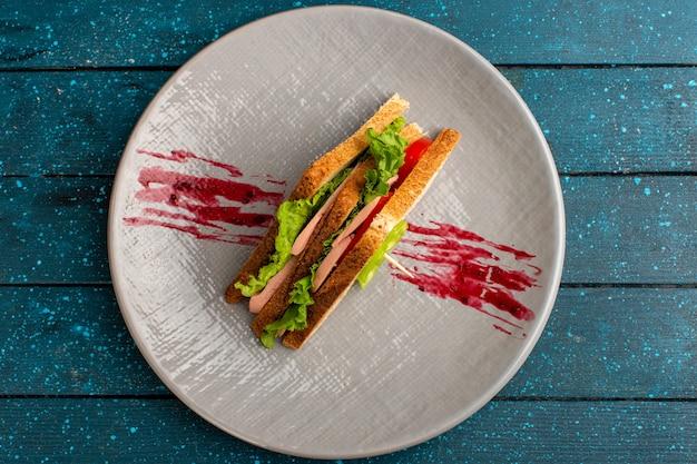 Vue de dessus de la plaque intérieure de sanwich sur la plaque blanche et bureau bleu