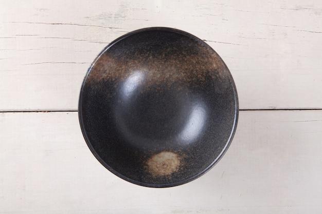 Vue de dessus de la plaque noire vide mise sur la table en bois blanc avec espace pour copie.