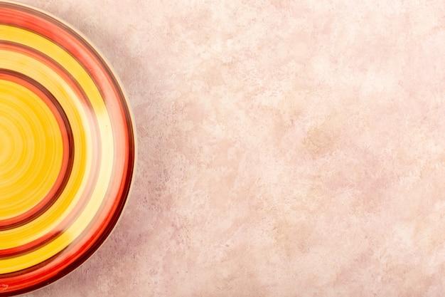 Une vue de dessus plaque ronde colorée en verre vide fait de couleur de table de repas isolé à rayures