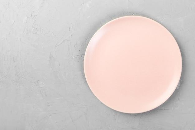 Vue de dessus de la plaque rose vide mate ronde sur l'espace de fond de ciment gris pour vous concevoir
